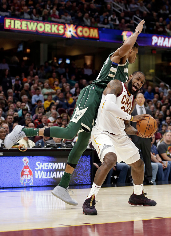 . Cleveland Cavaliers\' LeBron James, right, is fouled by Milwaukee Bucks\' Giannis Antetokounmpo, from Greece, in the first half of an NBA basketball game, Tuesday, Nov. 7, 2017, in Cleveland. (AP Photo/Tony Dejak)