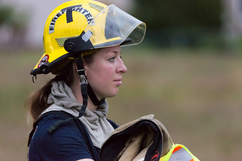 Yound female fire fighter relaxing after drill in Buckley, WA.