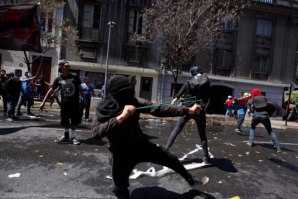 . Masked protesters clash with police after the end of a march against the commemoration of the discovery of America in Santiago, Chile, Saturday, Oct. 12, 2013. The march was organized by members of indigenous groups demanding autonomy and the recovery of ancestral land. Protesters also demonstrated against Chile\'s anti-terrorism law, under which many Mapuche Indians are under arrest. Saturday is the the anniversary of Christopher Columbus\' 1492 arrival in the Americas. (AP Photo/Luis Hidalgo)