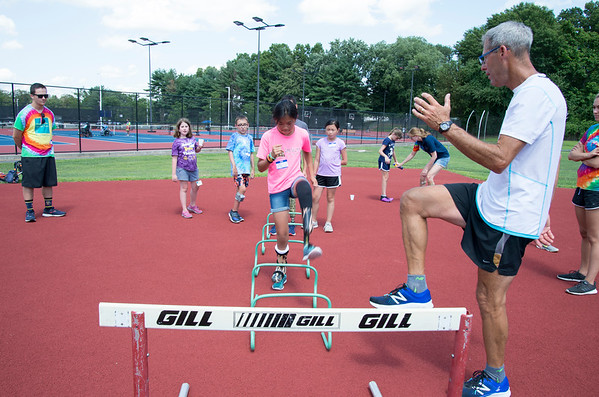 08/08/19 Wesley Bunnell | Staff Track and Field coach Bill Wilkie, R, demonstrates proper technique for warming up to campers including Sarah Reid at the Hospital for Special Care's Ivan Lendl Adaptive Sports Camp at Berlin High School on Thursday August 9, 2019.