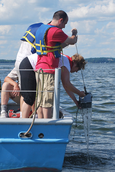 Mary Possin helps an open house attendee bring his sediment sample on board.