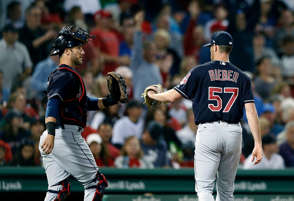 . Cleveland Indians\' Shane Bieber (57) and Yan Gomes return to the dugout during the fifth inning of a baseball game against the Boston Red Sox in Boston, Tuesday, Aug. 21, 2018. (AP Photo/Michael Dwyer)