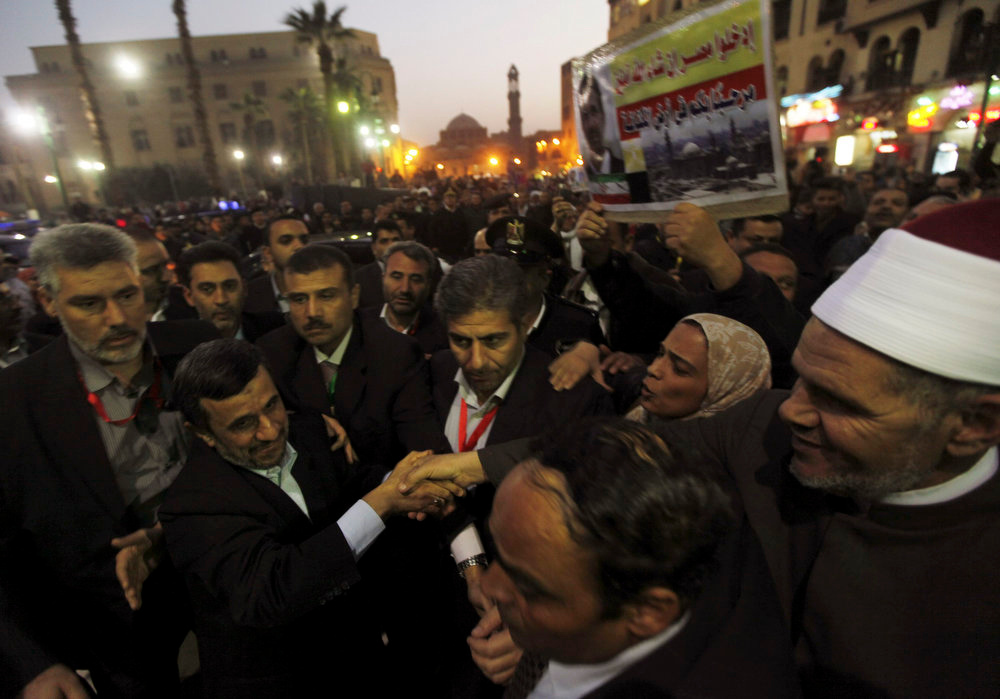 Description of . Iran's President Mahmoud Ahmadinejad (2nd L) shakes hands with a sheikh as he arrives in front of the Al-Hussein mosque, named after Prophet Mohammed's grandson Hussein ibn Ali, in old Cairo February 5, 2013. Ahmadinejad was both kissed and scolded on Tuesday when he began the first visit to Egypt by an Iranian president since Tehran's 1979 Islamic revolution. The trip was meant to underline a thaw in relations since Egyptians elected an Islamist head of state, President Mohamed Mursi, last June. But it also highlighted deep theological and geopolitical differences. REUTERS/Amr Abdallah Dalsh