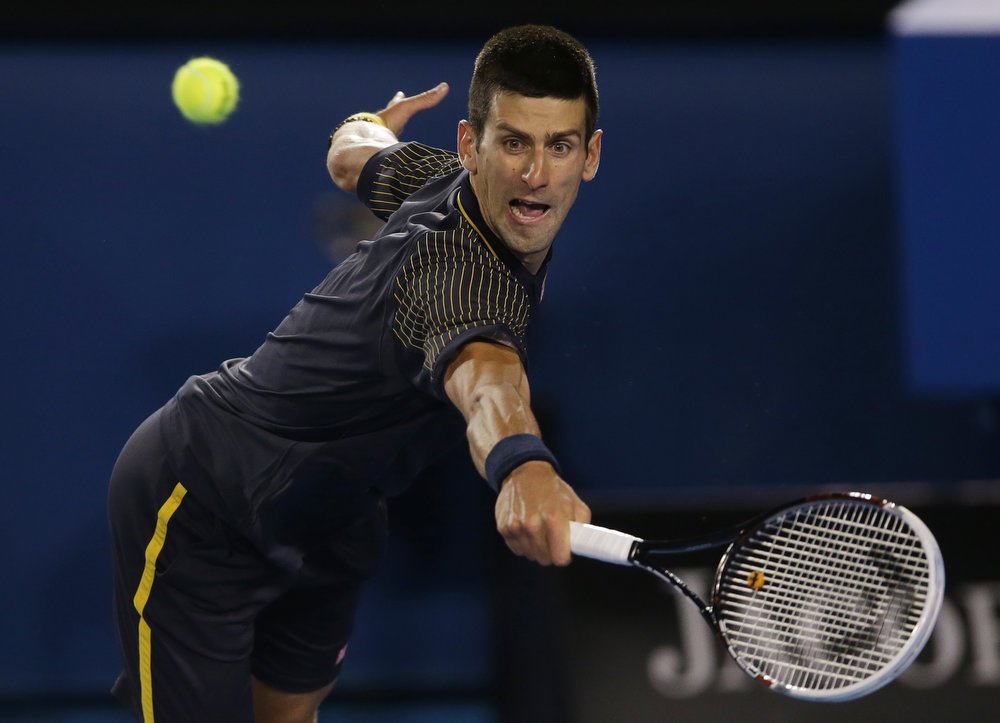 . Serbia\'s Novak Djokovic makes a backhand return to Britain\'s Andy Murray during the men\'s final at the Australian Open tennis championship in Melbourne, Australia, Sunday, Jan. 27, 2013. (AP Photo/Dita Alangkara)