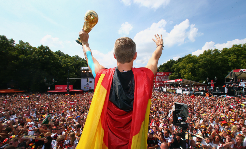 """. German soccer player Bastian Schweinsteiger celebrates on stage at the German team victory ceremony, near the Brandenburg Gate in Berlin,  Tuesday July 15,  2014.  Germany\'s World Cup winners shared their fourth title with hundreds of thousands of fans by parading the trophy through cheering throngs to celebrate at the Brandenburg Gate on Tuesday. An estimated 400,000 people packed the \""""fan mile\"""" in front of the Berlin landmark to welcome home coach Joachim Loew\'s team and the trophy � which returned to Germany for the first time in 24 years. (AP Photo/ Alex Grimm,Pool)"""