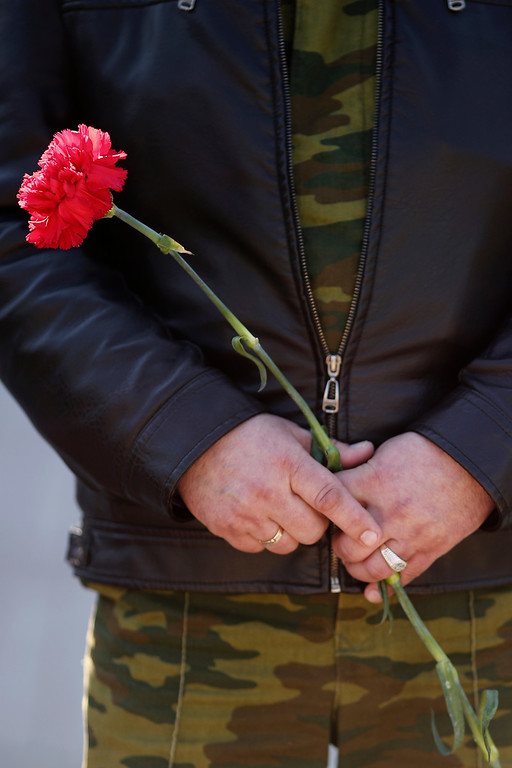 . A Cossack man holds a flower during a Pro Russian rally in Lenin Square on March 15, 2014 in Simferopol, Ukraine. As the standoff between the Russian military and Ukrainian forces continues in Ukraine\'s Crimean peninsula, world leaders are pushing for a diplomatic solution to the escalating situation. Crimean citizens will vote in a referendum tomorrow on whether to become part of the Russian federation.  (Photo by Dan Kitwood/Getty Images)