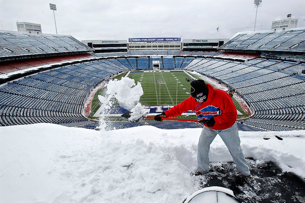 . Matt Kirsch clears snow from the top of the press box at Ralph Wilson Stadium before an NFL football game between the New York Jets and Buffalo Bills in Orchard Park, N.Y., Sunday, Dec. 30, 2012. (AP Photo/Mel Evans)
