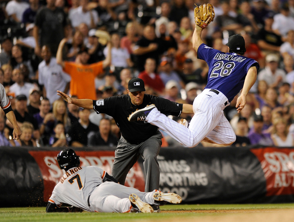 . Colorado Rockies third baseman Nolan Arenado (28) misses the tag on San Francisco Giants\' Gregor Blanco (7) at third during the seventh inning of a baseball game on Tuesday, Aug. 27, 2013, in Denver. Blanco hit a triple on the play.  (AP Photo/Jack Dempsey)