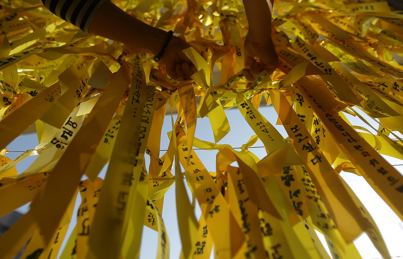 . A South Korean woman ties a yellow ribbon of hope for the safe return of missing passengers of sunken ferry Sewol at a group memorial altar  on May 1, 2014 in Seoul, South Korea. No survivors have been found since 174 passengers and crew were rescued on the day of the incident, April 16.  (Photo by Chung Sung-Jun/Getty Images)