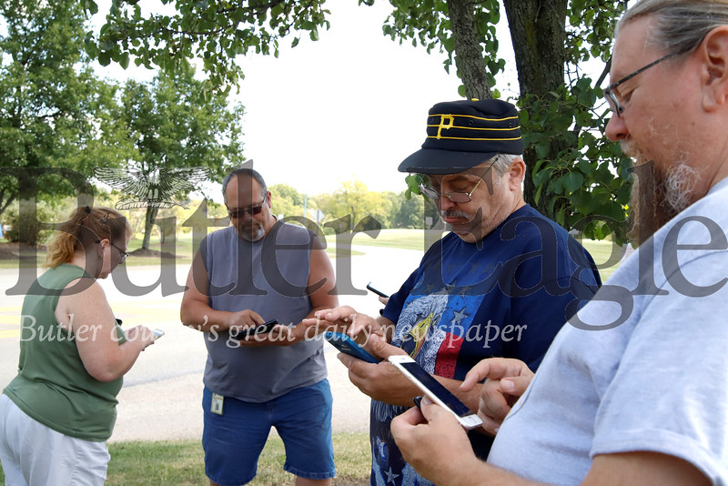 Andy Kuntz(right) Martin Gaynor, Dave and Susan Shoop take advantage of a sunny Thursday to meet up with other Pokemon Go enthusiasts for an EX Raid  to capture a rare Deoxys pokemon at Cranberry's North Boundary Park. The Shoops had four phones between them in order to play for their kids, 24 and 26, who were unable to attend. Seb Foltz/Butler Eagle