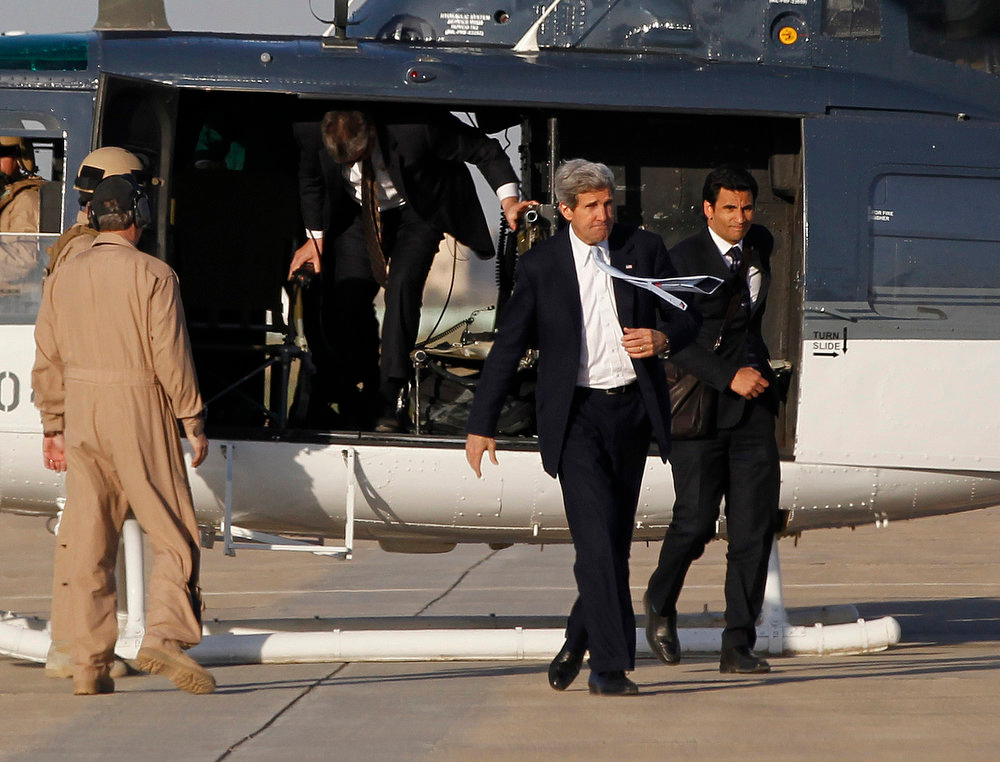 . U.S. Secretary of State John Kerry (2nd R) steps off a helicopter as he prepares to board an aircraft to leave Iraq at Baghdad International Airport March 24, 2013. Kerry made an unannounced visit to Iraq on Sunday and said he told Prime Minister Nuri al-Maliki of his concern about Iranian flights over Iraq carrying arms to Syria. REUTERS/Jason Reed