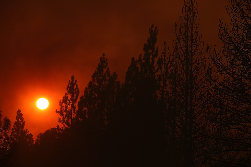 . GROVELAND, CA - AUGUST 21:  The sun sets through heavy smoke from the Rim Fire on August 21, 2013 in Groveland, California. The Rim Fire continues to burn out of control and threatens 2,500 homes outside of Yosemite National Park. Over 400 firefighters are battling the blaze that is only 5 percent contained.  (Photo by Justin Sullivan/Getty Images)