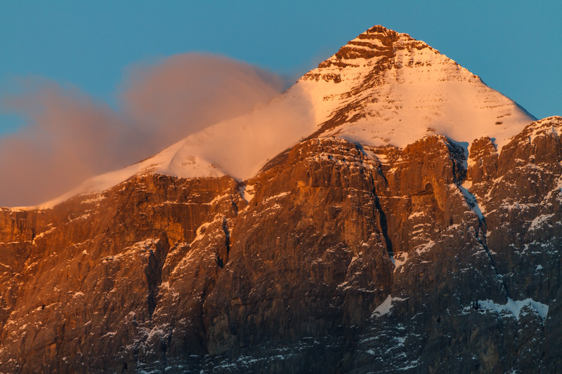 Towering mountain covered in snow as the sunsets