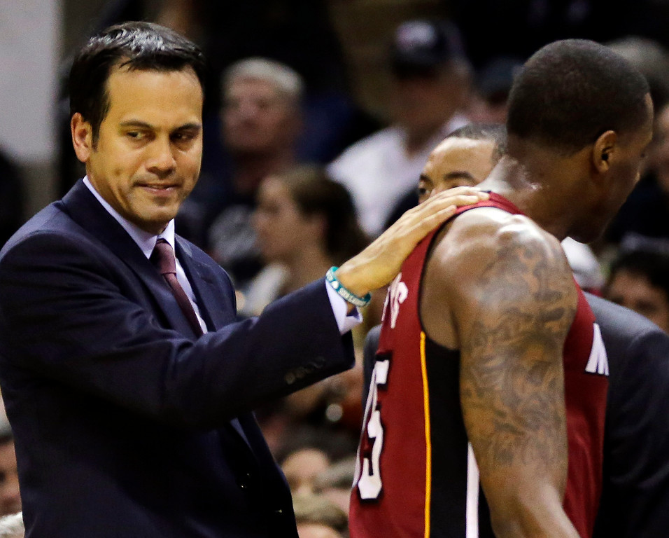 . Miami Heat head coach Erik Spoelstra, left, gives guard Mario Chalmers a pat on the sideline against the San Antonio Spurs during the second half in Game 1 of the NBA basketball finals on Thursday, June 5, 2014 in San Antonio. (AP Photo/Eric Gay)