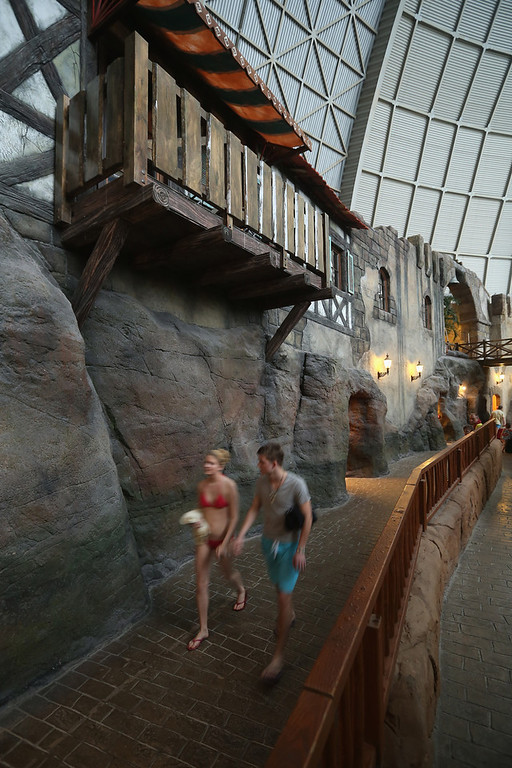 ". Visitors walk past the ""Alcantara Canyon\"" that includes lockers and rooms for overnight guests at the Tropical Islands indoor resort on February 15, 2013 in Krausnick, Germany. Located on the site of a former Soviet military air base, the resort occupies a hangar built originally to house airships designed to haul long-distance cargo. Tropical Islands opened to the public in 2004 and offers visitors a tropical getaway complete with exotic flora and fauna, a beach, lagoon, restaurants, water slide, evening shows, sauna, adventure park and overnights stays ranging from rudimentary to luxury. The hangar, which is 360 metres long, 210 metres wide and 107 metres high, is tall enough to enclose the Statue of Liberty.  (Photo by Sean Gallup/Getty Images)"
