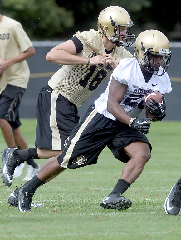 . University of Colorado\'s Tony Jones runs the ball in front of quarterback Stevie Joe Dorman during the second fall football practice on Wednesday, Aug. 7, at the CU practice fields. For more photos of practice go to www.dailycamera.com Jeremy Papasso/Camera