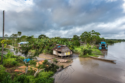 Wide view of Amazon village with shacks and large blue boat