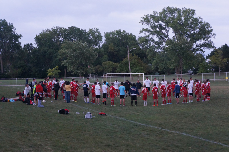 Alumni & team members gathering in prayer after the 10th Annual Alumni Soccer Game at Lutheran West.