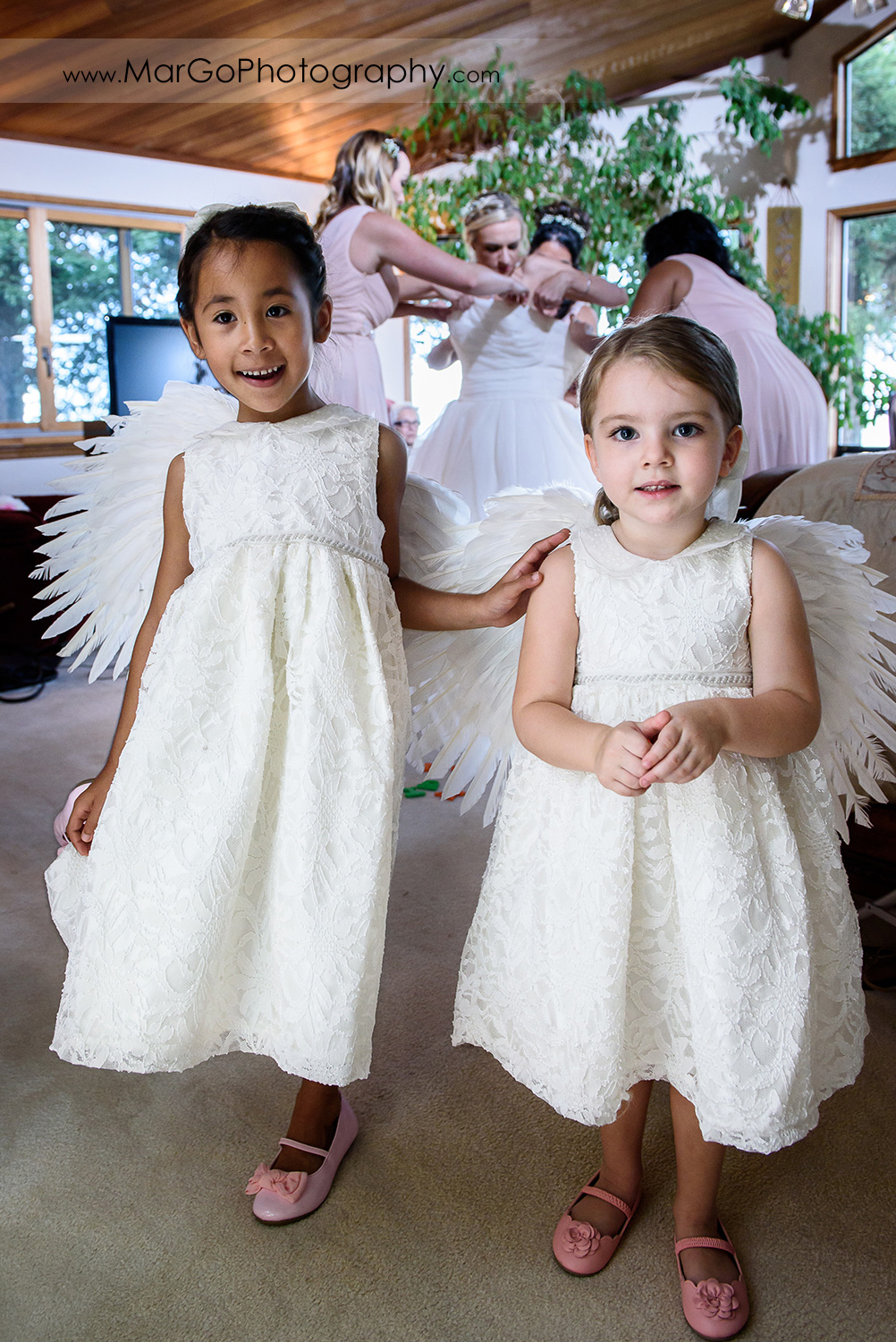 flower girls in white dresses with bride gettinf ready in the background