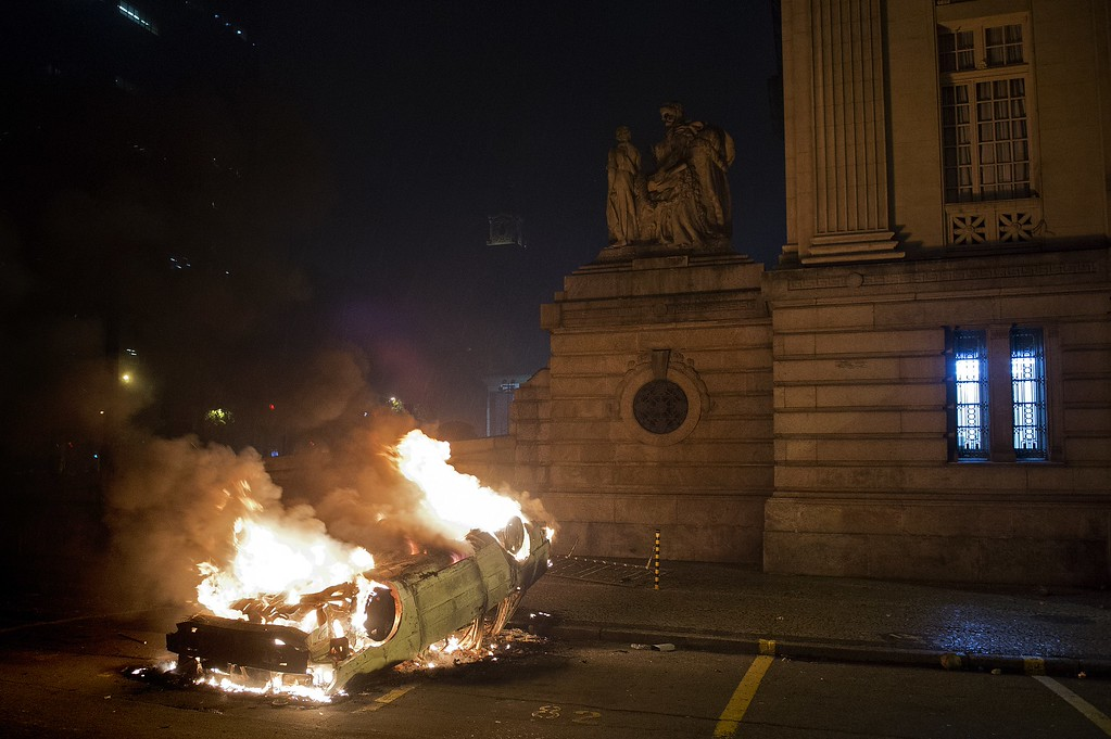 . A car set on fire by demonstrators burns in front of the state Legislative Assembly (ALERJ) building in Rio de Janeiro downtown, during a protest on June 17, 2013. Tens of thousands of people took to the streets of major Brazilian cities protesting the billions of dollars spent on the Confederations Cup --and preparations for the upcoming World Cup-- and against the hike in mass transit fares.    PABLO PORCIUNCULA/AFP/Getty Images