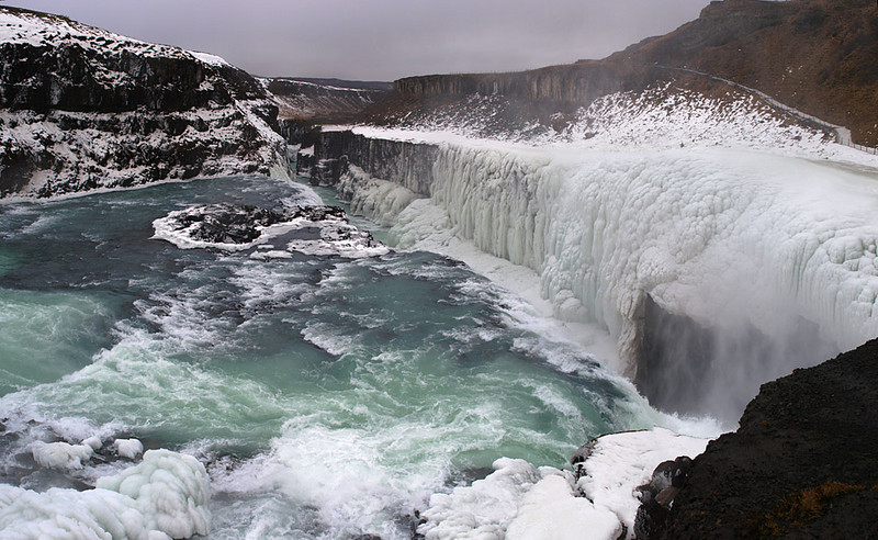 """Gullfoss (Golden Falls) is a massive waterfall located in the canyon of Hvítá river in southwest Iceland.  It is is one of the most popular tourist attractions in the country. The wide Hvítá rushes southward and 1km above the falls it turns sharply to the left and flows down into a wide curved three-step """"staircase"""" and then abruptly plunges in two stages into a crevice 105 ft deep. The crevice is 60 ft wide, and 2.5 km in length, is at right angles to the flow of the river.   The part frozen falls took my breath away as I first approached. Spectacular is just not grand enough to describe it. I trust the pictures help. Nice shot of the long crevice, I got a bit edge close to get this shot. Olympus E3, 12-60mm SWD."""