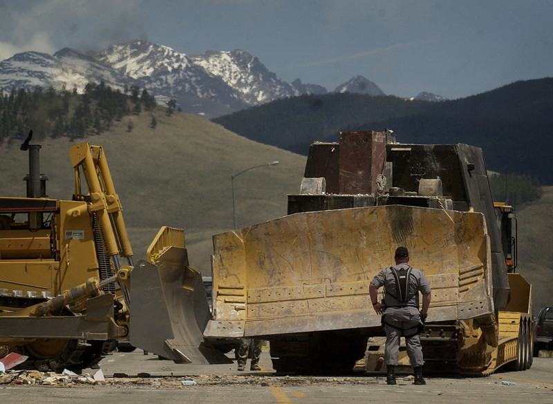 . An officer on Main St. looks over the vehicle that caused havoc in downtown Granby, CO, June 5, 2004. Workers spent close to 3 hours removing  the fortified bulldozer  driven by Marvin Heemeyer from downtown Granby, where it came to rest at Gambles of Grand County on highway 40 in Granby, CO. Heemeyer drove a fortified bulldozer through the streets of Granby Friday destroying a number of buildings.   (DENVER POST PHOTO BY HYOUNG CHANG)