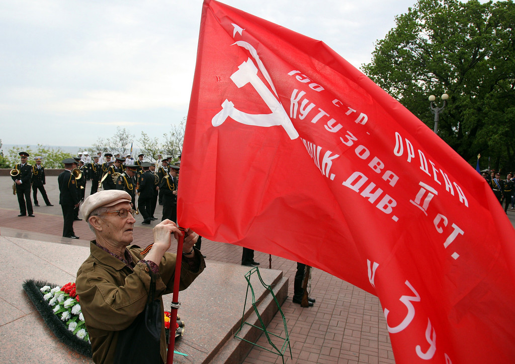 . A man erects a red flag bearing a hammer and a sickle at the Unknown Sailor Memorial on Victory Day in the southern Ukrainian city of Odessa on May 9, 2014. Russian President Vladimir Putin took a victory lap in his first visit to Crimea since its annexation by Russia, as fighting in eastern Ukraine left at least 21 dead just days ahead of a separatist vote. AFP PHOTO/ ANATOLII STEPANOV/AFP/Getty Images