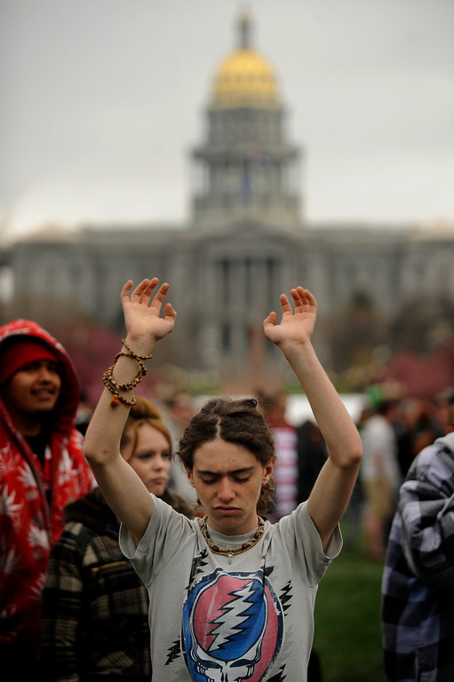 . 17 year old Nick Reed of Littleton prays to the spirt of the north during the Native American Blessing to start the Annual Denver 420 Rally in Civic Center Park.      Joe Amon, The Denver Post