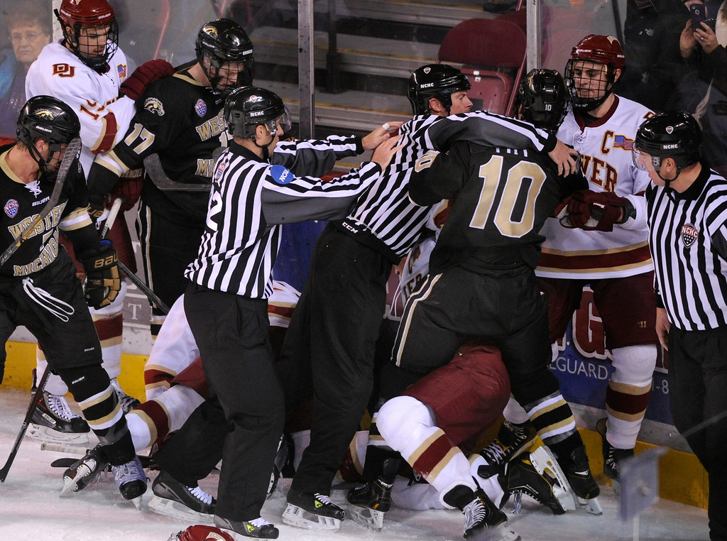 . DENVER, CO. - NOVEMBER 16: Officials untangled players at the end of the game. The University of Denver hockey team defeated Western Michigan 1-0 at Magness Arena Saturday night, November 16, 2013.  Photo By Karl Gehring/The Denver Post