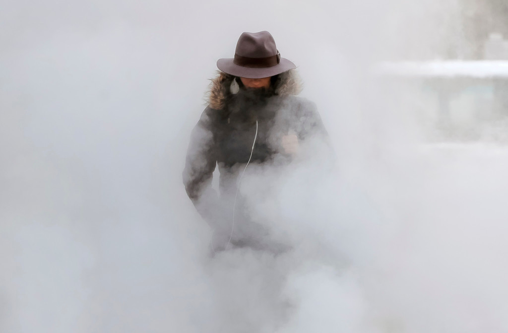 . A woman walks through steam from an underground ventilation, as temperatures dropped below minus 20 degrees Centigrade ( minus 4 Fahrenheit) in Bucharest, Romania, Tuesday, Jan. 10, 2017. Romania\'s Energy Minister Toma Petcu said neighboring Bulgaria had urgently asked for extra electricity, but the request was declined since the cold weather has stretched Romania\'s power grid and natural gas consumption in Romania could reach an all-time high due to the frigid temperatures. (AP Photo/Vadim Ghirda)