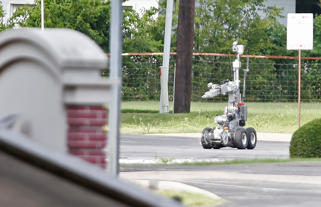 . Dallas Police use a robot to gain access to an armored van, which authorities believed was rigged with explosives, and was driven by a suspect who attacked Dallas Police Headquarters in Dallas, Texas, June 13, 2015. A lone shooter in an armored van, believed to be rigged with explosives, opened fire on the Dallas Police Headquarters early Saturday morning. The shooter reportedly unleashed multiple rounds and planted explosive devices around the station before leading police on a chase that ended in a standoff in the parking lot of a fast food restaurant. (Photo by Stewart F. House/Getty Images)