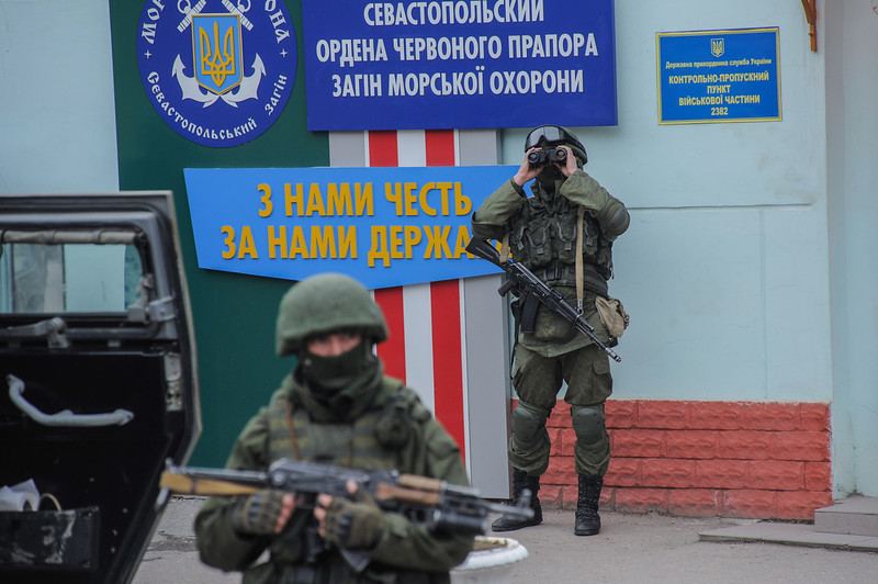 . Troops in unmarked uniforms stand guard as they taking control the the Caost Guard offices in Balaklava on the outskirts of Sevastopol, Ukraine, Saturday, March 1, 2014. An emblem on one of the vehicles and their number plates identify them as belonging to the Russian military. Ukrainian officials have accused Russia of sending new troops into Crimea, a strategic Russia-speaking region that hosts a major Russian navy base. The Kremlin hasn\'t responded to the accusations, but Russian lawmakers urged Putin to act to protect Russians in Crimea. (AP Photo/Andrew Lubimov)