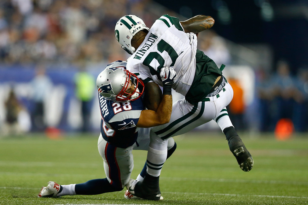 . Tight end Kellen Winslow #81 of the New York Jets is tackled by strong safety Steve Gregory #28 of the New England Patriots in the first half at Gillette Stadium on September 12, 2013 in Foxboro, Massachusetts.  (Photo by Jared Wickerham/Getty Images)