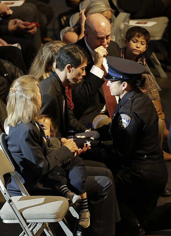 . Peter Wu accepts a U.S. flag after a memorial service for his slain partner, Santa Cruz police detective Elizabeth Butler, at a memorial service Thursday, March 7, 2013, at HP Pavilion  in San Jose, Calif. Butler was shot shot to death on Feb. 27, after arriving at the home of Jeremy Peter Goulet to question him about a misdemeanor sexual assault. (AP Photo/Ben Margot)