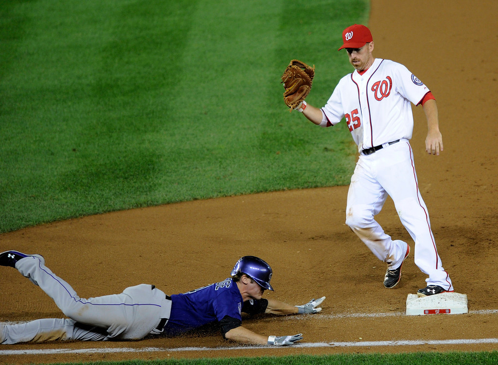 . Colorado Rockies\' Josh Rutledge, bottom, slides towards first as Washington Nationals first baseman Adam LaRoche, top, steps on the bag for the out during the ninth inning of a baseball game, Friday, June 21, 2013, in Washington. The Nationals won 2-1. (AP Photo/Nick Wass)