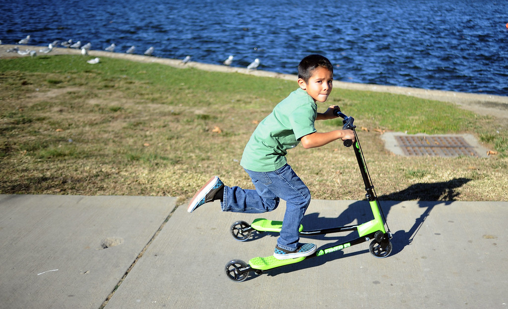 . Tony Rodarte, 6-years-old, rides his new scooter while enjoying the warm weather at Lake Balboa in Anthony C. Beilenson Park in Van Nuys on Christmas day. (Photo by Hans Gutknecht/Los Angeles Daily News)