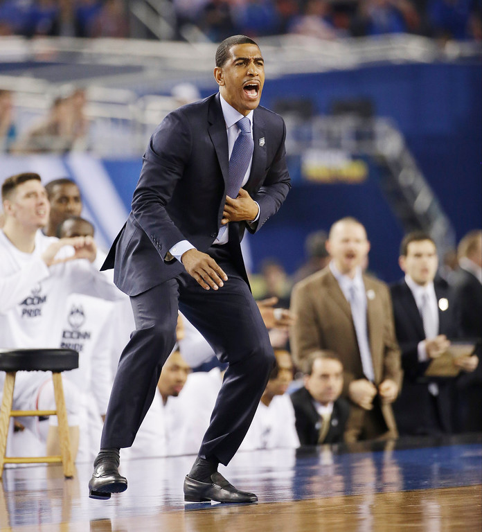 . Connecticut head coach Kevin Ollie directs action from the sideline against Kentucky during the first half of the NCAA Final Four tournament college basketball championship game Monday, April 7, 2014, in Arlington, Texas. (AP Photo/David J. Phillip)