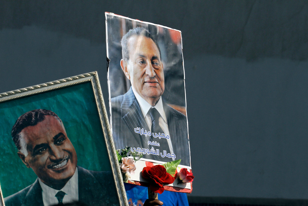 ". Supporters of Egypt\'s former President Hosni Mubarak raise his poster and one of late President Gamal Abdel Nasser, left, in front of Torah Prison where Mubarak has been held, in Cairo, Egypt, Thursday, Aug. 22, 2013. Arabic writing on the poster reads ""Mubarak lovers.\"" Egypt\'s ousted leader Hosni Mubarak, wearing a white shirt and loafers while flashing a smile, was released from prison Thursday and transported to a military hospital in a Cairo suburb where he will be held under house arrest. (AP Photo/Amr Nabil)"
