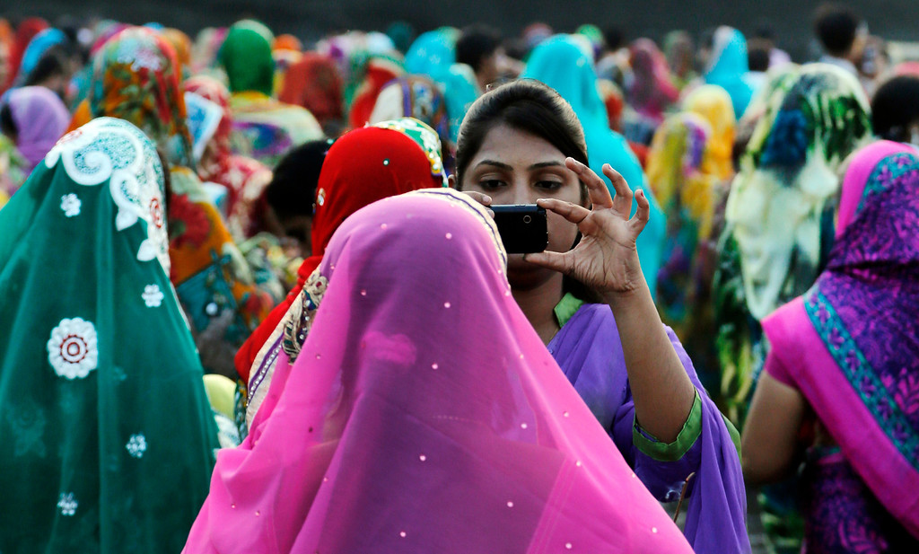 . A young Hindu girl takes a photograph of her relative as they gather on the banks of the Arabian Sea to perform rituals on Chhath Puja festival in Mumbai, India, Friday, Nov. 8, 2013.  (AP Photo/Rajanish Kakade)