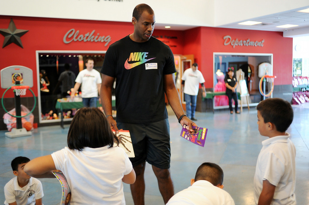 . NBA player Jason Collins gives children books during MEND�s (Meet Each Need with Dignity) 13th annual �Head to Toes,� program at the Pacoima charity�s center Wednesday, August 27, 2014. 240 third-graders from Pacoima�s Vaughn Next Century Learning Center were provided with full back-to-school care: free dental and vision screenings through a healthcare initiative with Verizon Foundation, new shoes and new backpacks chock-full of school supplies school supplies donated by the Ella Fitzgerald Charitable Foundation. (Photo by Hans Gutknecht/Los Angeles Daily News)