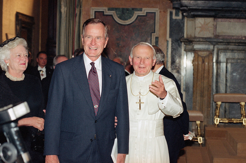 . Pope John Paul II invites U.S. President George Bush, accompanied by his wife, Barbara, to meet members of the clergy gathered in the Vatican\'s Clementine Hall, Friday, Nov. 8, 1991. The President and the Pope met after the President attended the NATO Summit in Rome. (AP Photo/Denis Paquin)