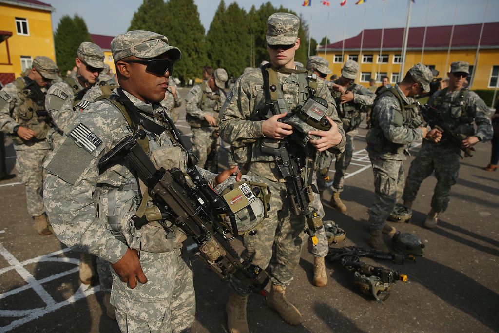 ". Members of the U.S. Army 173rd Airborne Brigade prepare weapons and equipment following the opening ceremony of the ""Rapid Trident\"" NATO military exercises on September 15, 2014 near Yavorov, Ukraine.  (Photo by Sean Gallup/Getty Images)"