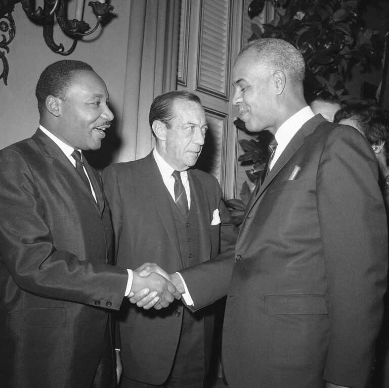 . Rev. Martin Luther King, left, shakes hands with Roy Wilkins, executive director of the National Association for the Advancement of Colored People, at a reception given for King by New York City Mayor Robert Wagner, center, on Dec. 17, 1964. King returned after receiving the Nobel Peace Prize in Oslo, Norway. (AP Photo/Marty Lederhandler)