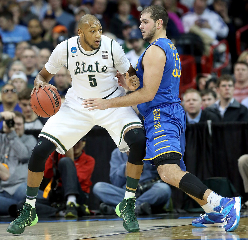 . Adreian Payne #5 of the Michigan State Spartans drives on Carl Baptiste #33 of the Delaware Fightin Blue Hens during the second round of the 2014 NCAA Men\'s Basketball Tournament at Spokane Veterans Memorial Arena on March 20, 2014 in Spokane, Washington.  (Photo by Stephen Dunn/Getty Images)