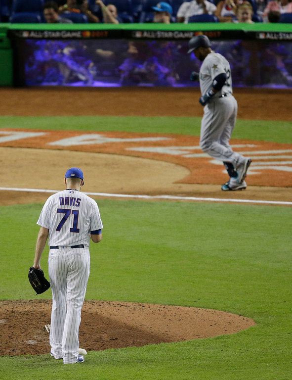 . National League\'s Chicago Cubs pitcher Wade Davis (71) looks down as American League\'s Seattle Mariners Robinson Cano (22), approaches home plate after hitting a home run in the tenth inning, during the MLB baseball All-Star Game, Tuesday, July 11, 2017, in Miami. The American League defeated the National League 2-1. (AP Photo/Alan Diaz)