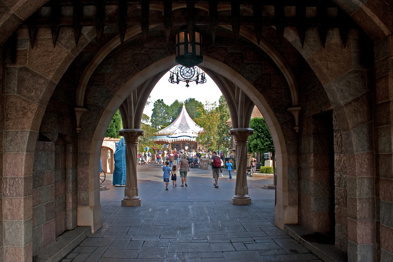 Looking through the Sleeping Beauty Castle entrance into Fantasyland, with the King Arthur Carousel in teh background.