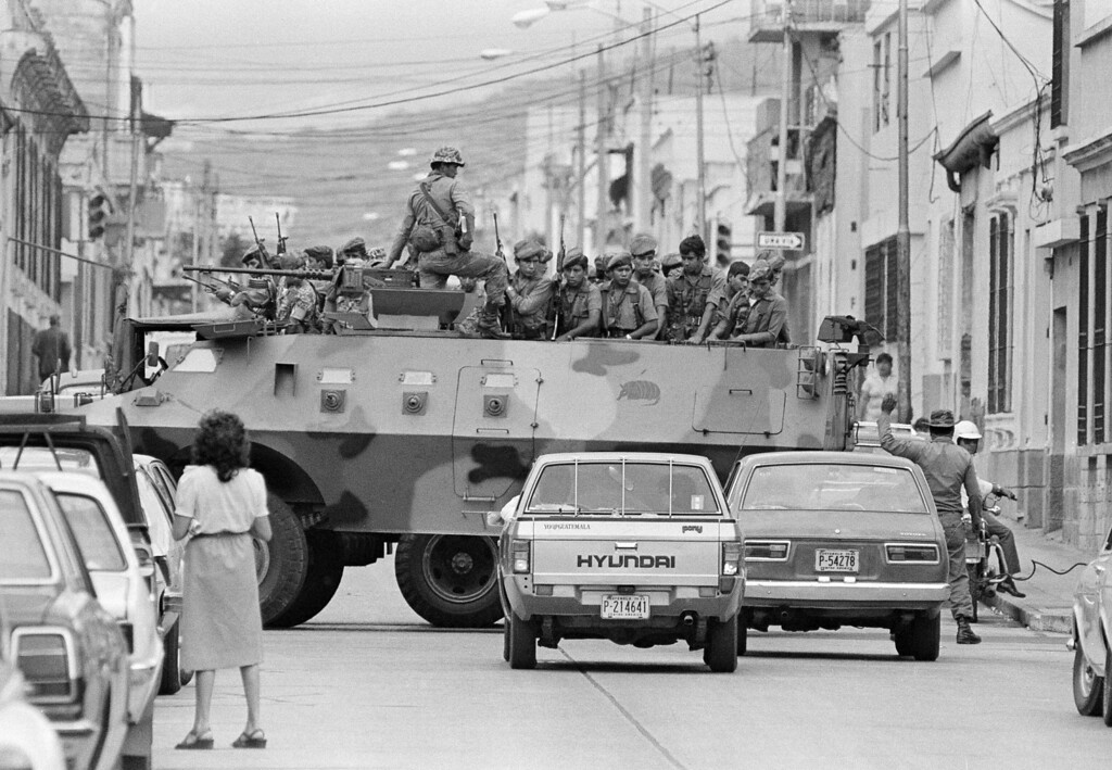 . An armored troop carrier and a truckload of Guatemalan soldiers block an intersection near the Presidential Palace in downtown Guatemala City, Aug. 10, 1983. Government troops were seen throughout the city one day after the government of Gen. Efrain Rios Montt was toppled by a military coup. Defense Minister Gen. Oscar Humberto Mejia Victores was named president. (AP Photo/P.W. Hamilton)