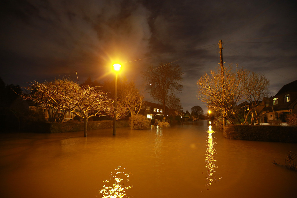 . Flood water fills the road as night falls on February 11, 2014 in Wraysbury, England. Some home owners say that they will stay in their homes even though they have been offered help to evacuate as flood water rises.  (Photo by Peter Macdiarmid/Getty Images)