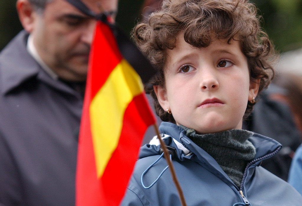 . A young girl holds a Spanish flag with a black ribbon, in the courtyard of the residence of the Spanish ambassador to Portugal, Lisbon, Friday, March 12 2004, where people gathered for a minute\'s silence for the victims of Thursday\'s railway bombings in Madrid, Spain. (AP Photo/Armando Franca)