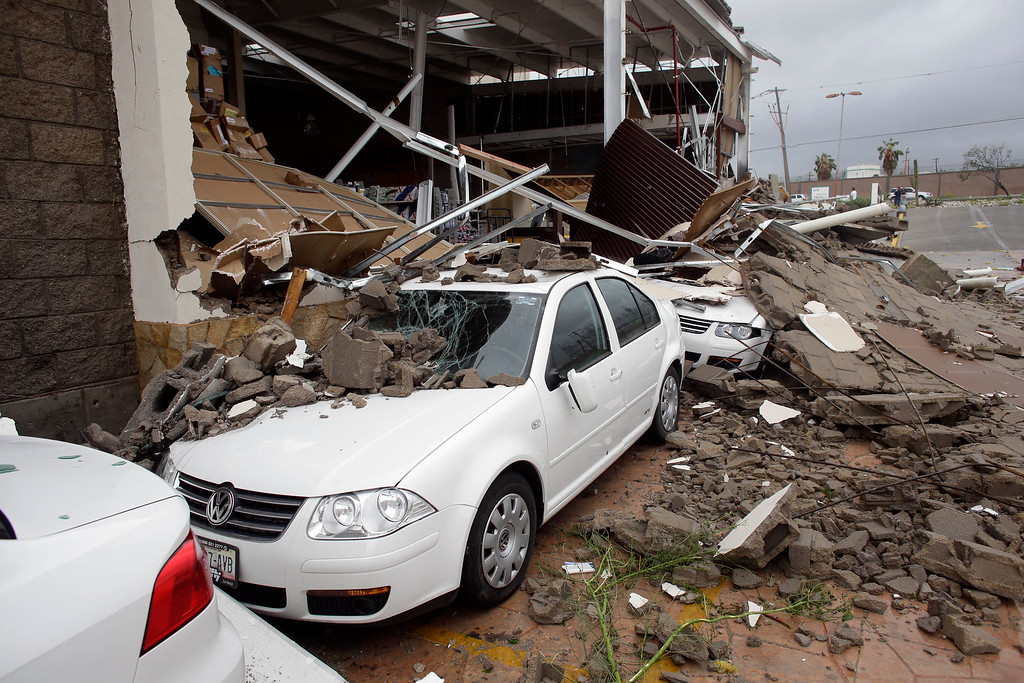. Cars parked next to an office supplies store partially destroyed by Hurricane Odile, in Los Cabos, Mexico,  Monday, Sept. 15, 2014. (AP Photo/Victor R. Caivano)